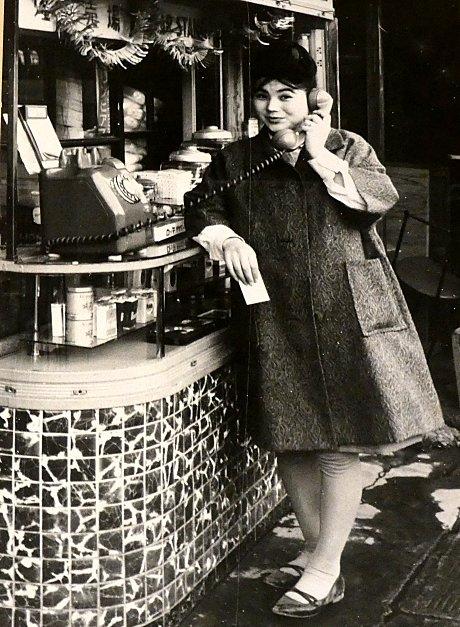 公衆電話をかける女性